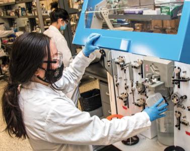Inside Precision Nanosystems a worker adjusts a machine